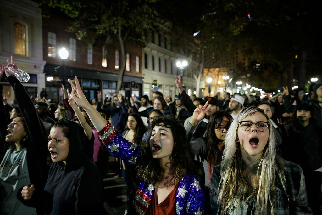 Demonstrators Madeline Lopes (center) and Cassidy Irwin (right) protested against president-elect Donald Trump in Oakland, California, U.S., November 9, 2016. Another group earlier in the night set fire to garbage bins and smashed multiple windows. Photo: Gabrielle Lurie, The Chronicle