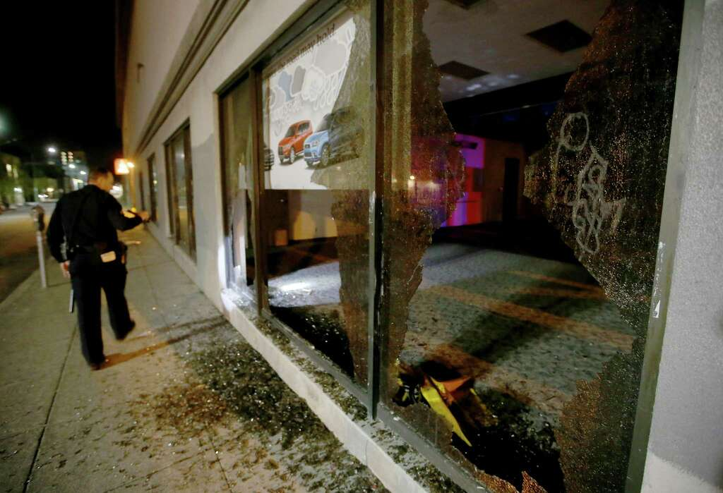 An Oakland police officer checks out damage after a window was broken by protesters at a car dealership in downtown Oakland, Calif., on Wednesday, Nov. 9, 2016. President-elect Donald Trump's victory set off multiple protests. (Jane Tyska/Bay Area News Group via AP) Photo: Jane Tyska, AP / THE OAKLAND TRIBUNE/BAY AREA NEWS GROUP/DIGITAL FIRST MEDIA