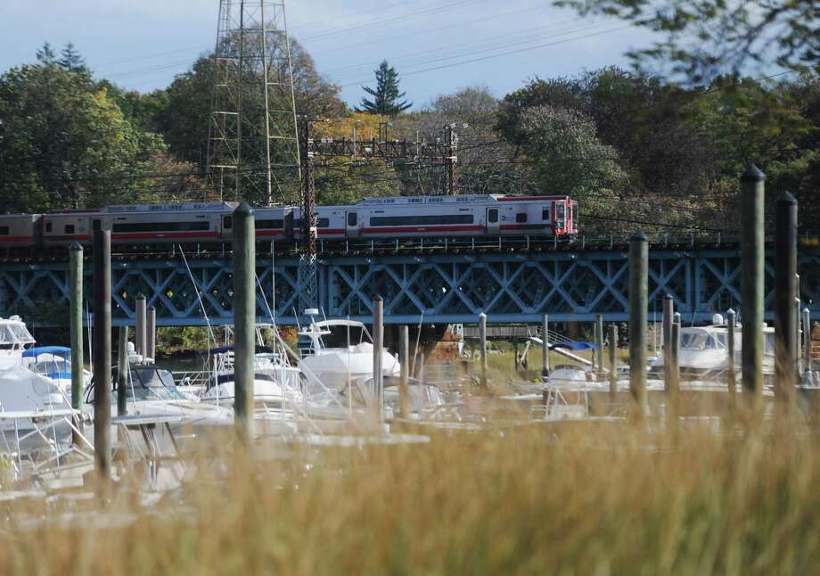 A southbound Metro-North train passes across the railroad bridge spanning Cos Cob Harbor in the Cos Cob section of Greenwich, Conn. Tuesday, Oct. 25, 2016. The 1904 movable bridge did not close properly after it opened to allow river traffic to pass Tuesday morning, causing delays for commuters aboard the New Haven line trains. Photo: Tyler Sizemore / Hearst Connecticut Media / Greenwich Time