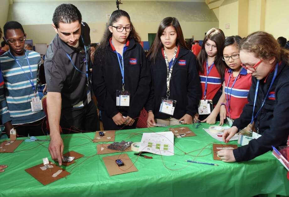 Harmony School student Muna Uba, left, join stem instructor Ernesto Preciodo and students Itzia Abrego, Julie Nguyen, Sarah, Hilary Huynh, and Jasmine Bagythai as they work to build a project to communicate with paper, wires and aluminum to send morse code. Photo: Tony Gaines, Photo