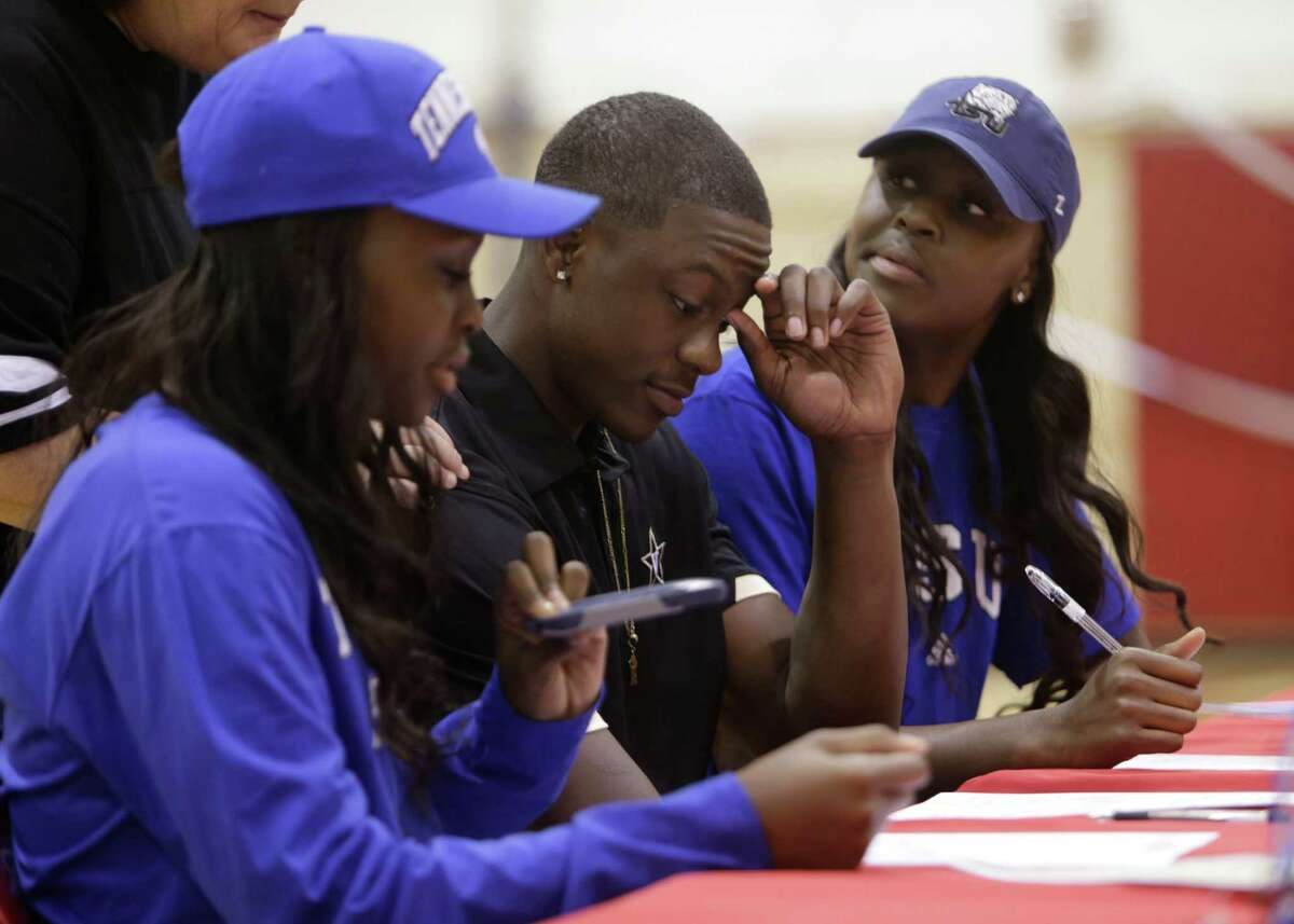 Triplets (LtoR) Megan, Maxwell and Maya Evans sign letters of intent during a ceremony at Bellaire High School, Wednesday, Nov. 9, 2016. Megan and Maya intend on attending Tennessee Tech University while Maxwell is signing with Vanderbilt University.
