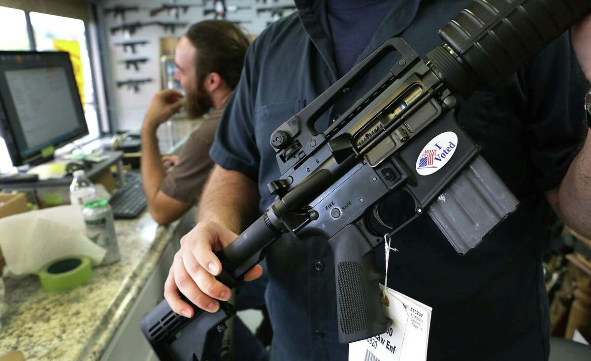 """A sales clerks at Adelbridge & Co. Firearms holds a rife that he put an """"I voted"""" sticker on in the north side store on Friday, Nov. 4, 2016."""