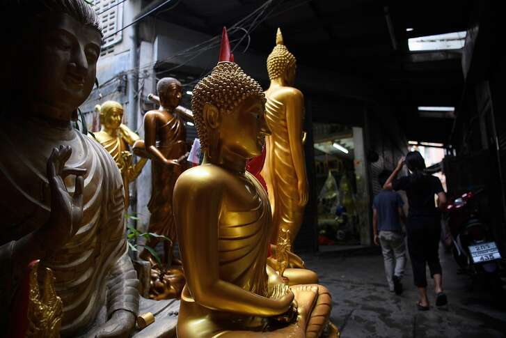 """BANGKOK, THAILAND - OCTOBER 17:  Religious idols are stored in an alley outside a storekeepers workshop on October 17, 2016 in Bangkok, Thailand. Despite Thai law prohibiting the export of Buddha images that are bigger than 5"""" without first obtaining an export permit, many stalls and stores offer a wide range of large-scale idols for sale.  (Photo by Leon Neal/Getty Images)"""
