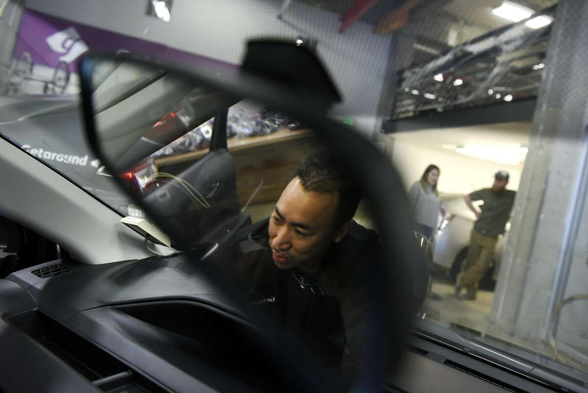 Auto technician Crosby Chan is reflected in a rearview mirror as he installs a Getaround Connect hardware device into a City CarShare vehicle in the garage at Getaround's offices in San Francisco, CA, Wednesday, November 9, 2016. Getaround, which arranges car rentals by the hour or day, is partnering with SF's City CarShare, and will manage its fleet of 200 cars.
