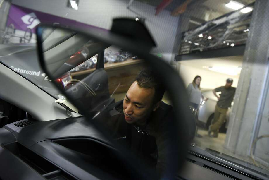 Auto technician Crosby Chan is reflected in a rearview mirror as he installs a Getaround Connect hardware device into a City CarShare vehicle in the garage at Getaround's offices in San Francisco, CA, Wednesday, November 9, 2016.   Getaround, which arranges car rentals by the hour or day, is partnering with SF's City CarShare, and will manage its fleet of 200 cars. Photo: Michael Short, Special To The Chronicle