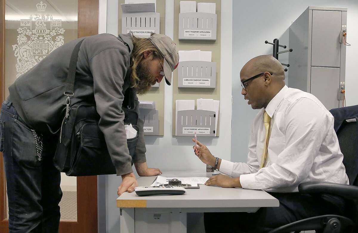 James Conrad (left) asks for an immigration form at the Canadian consulate on Wednesday, November 9, in San Francisco.