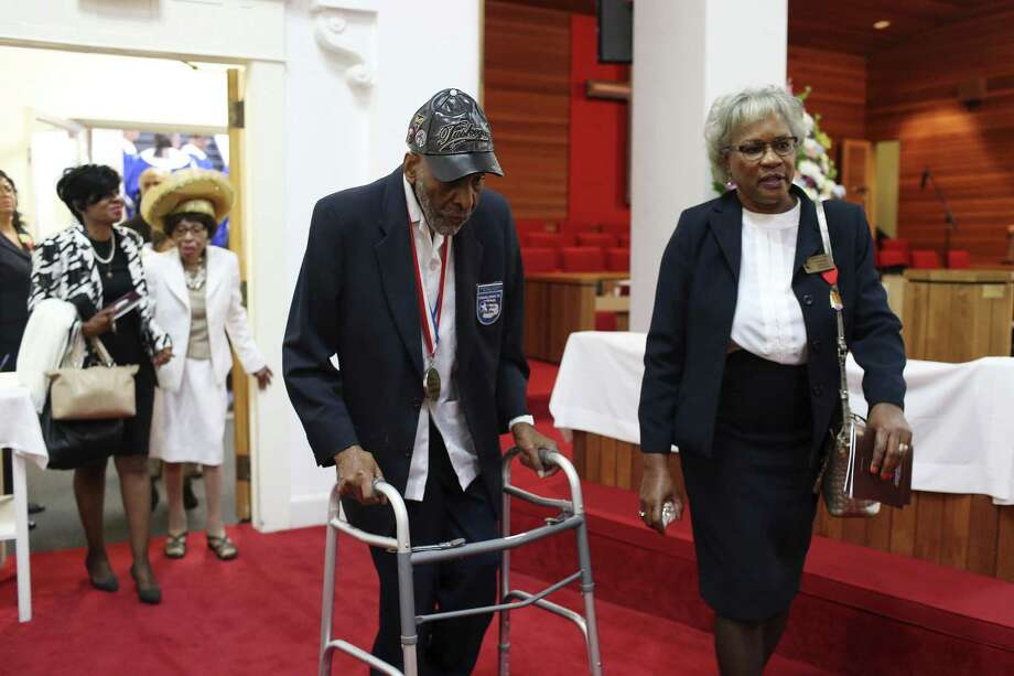 Carolin Sinkfield, right, escorts Tuskegee Airman Dr. Granville Coggs, 91, before St. Paul United Methodist Church celebration of its 150th anniversary service, Sunday, Nov. 6, 2016. It is the city's oldest African American church. Over the years, the church has been host to prominent civil rights figures, including Thurgood Marshall, Langston Hughes and A. Philip Randolph. The church was organized in 1866, one year after slavery ended, by freedmen and former slaves. The church's first pastor, the Rev. Larkin Carper served as a Union soldier with the 79th Regiment U.S. Colored Infantry, later known as the 1st Regiment Kansas Colored Company F. Photo: JERRY LARA, Staff / San Antonio Express-News / © 2016 San Antonio Express-News