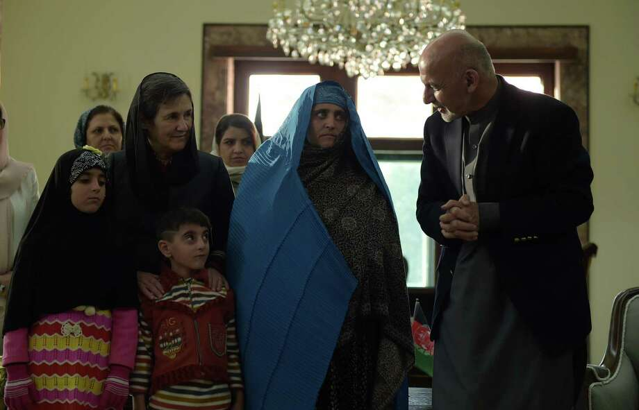 Afghan President Ashraf Ghani, right, talks with Sharbat Gula, the woman who became the face of Afghanistan's refugees abroad, on Wednesday at the Presidential Palace in Kabul. Photo: SHAH MARAI, Staff / AFP or licensors