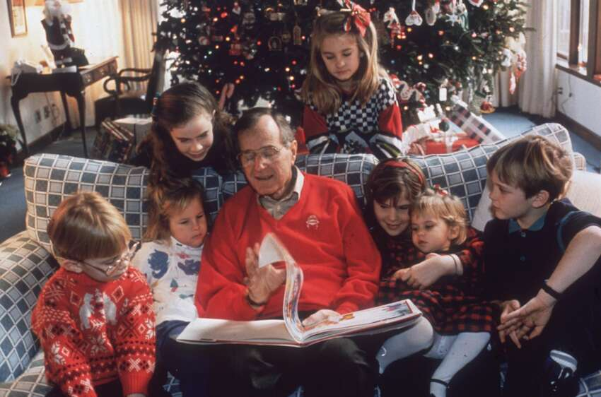 24th November 1991: American statesman George Bush, the 41st President of the United States, reading a Christmas story to his grandchildren on Christmas Eve at the White House, Washington DC. (Photo by Susan Biddle/Keystone/CNP/Getty Images)
