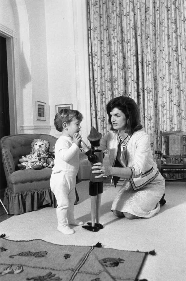 November 1962:  American First Lady Jacqueline Bouvier Kennedy (1929 - 1994) kneels on the floor with her son, John F. Kennedy, Jr. (1960 - 1999), playing with a wooden toy figure, inside the White House, Washington, D.C. There is a rag doll on the chair behind them.  (Photo by John F. Kennedy Library/John F. Kennedy Library/Getty Images) Photo: John F. Kennedy Library/Getty Images