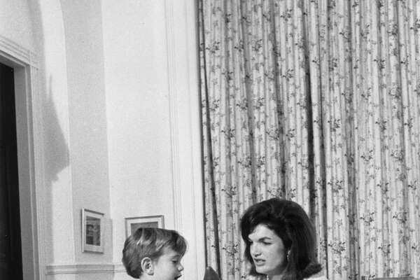 November 1962: American First Lady Jacqueline Bouvier Kennedy (1929 - 1994) kneels on the floor with her son, John F. Kennedy, Jr. (1960 - 1999), playing with a wooden toy figure, inside the White House, Washington, D.C. There is a rag doll on the chair behind them. (Photo by John F. Kennedy Library/John F. Kennedy Library/Getty Images)
