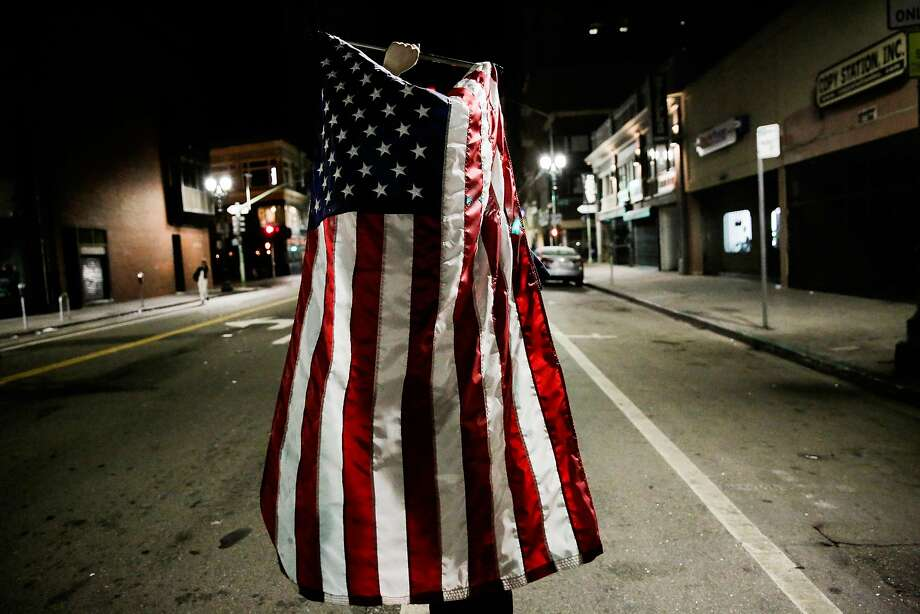 A man (who wished to remain anonymous) held a flag while walking in a demonstration against president-elect Donald Trump marched peacefully through Oakland, California, U.S., November 9, 2016. Photo: Gabrielle Lurie, The Chronicle