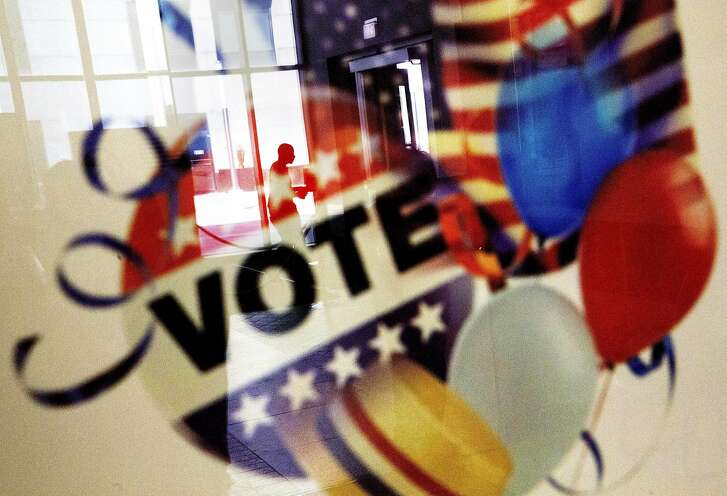 In this Nov. 1, 2016, photo, a voter is reflected in the glass frame of a poster while leaving a polling site in Atlanta, during early voting ahead of the Nov. 8 election day. If all goes smoothly, the American people will choose a new president on Tuesday, the Electoral College will affirm the election and either Democrat Hillary Clinton or Republican Donald Trump will take the oath of office Jan. 20.  (AP Photo/David Goldman)