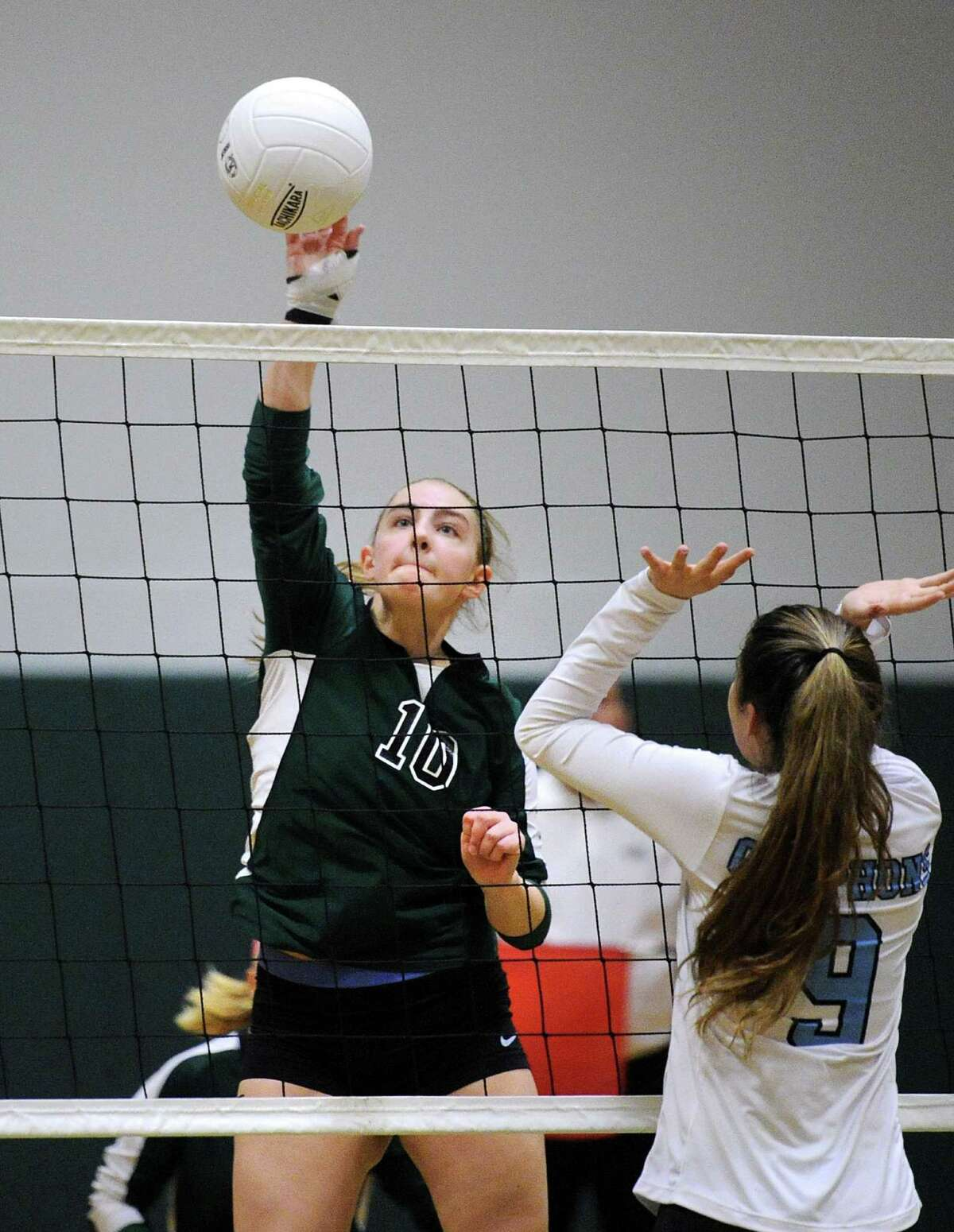 At left, Katie Kablack (10) of Sacred Heart spikes the ball as Holy Child's Caitlin Kaplan (9) defends during the girls high school FAA semi-final volleyball playoff match between Sacred Heart Greenwich and School of the Holy Child at Sacred Heart in Greenwich, Conn., Wednesday, Nov. 9. 2016. Sacred Heart beat Holy Child 3-0 to advance to the final.