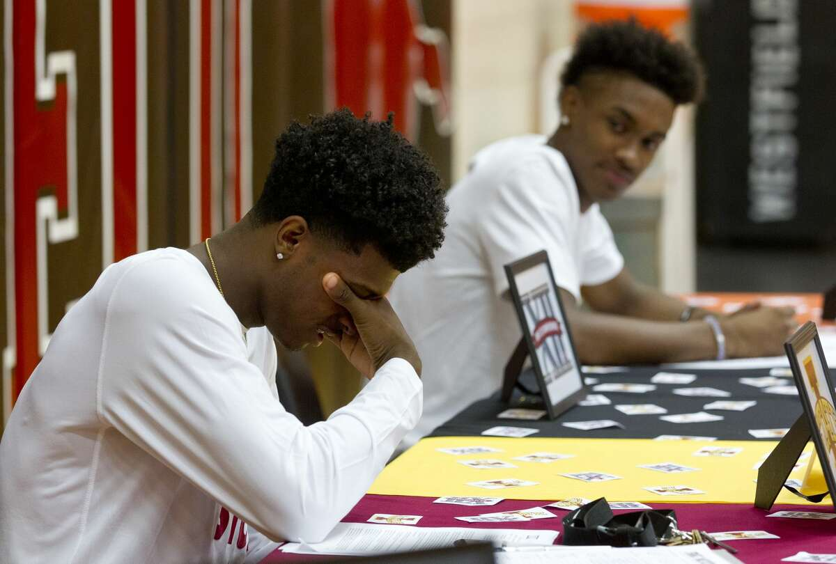 Westfield basketball player Darius McNeil, left, becomes emotional as he talks about his journey to signing with Iowa State University as teammate and University of Texas signee Jase Febres looks on during a national signing day ceremony at Westfield High School Wednesday, Nov. 9, 2016, in Spring.