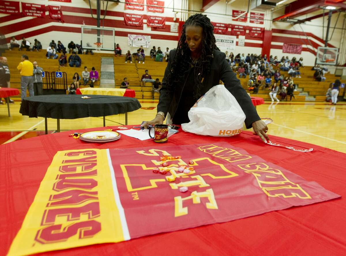 Kimberley Kelton, aunt of Jase Febres, helps lay out a display for teammate Darius McNeil during a national signing day ceremony at Westfield High School Wednesday, Nov. 9, 2016, in Spring. McNeil signed to play basketball at Iowa State University, while Febres will play for the University of Texas.