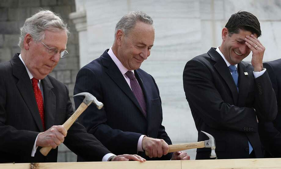 """WASHINGTON, DC - SEPTEMBER 21:  Speaker of the House Paul Ryan (R) (R-WI) laughs as Sen. Chuck Schumer (C) (D-NY) and Senate Majority Leader Mitch McConnell drive nails into a piece of lumber at the """"First Nail Ceremony"""" September 21, 2016 outside the U.S. Capitol in Washington, DC. The ceremony marked the official launch of construction on the Inaugural platform where the next President of the United States will take the oath of office on Friday, January 20, 2017.  (Photo by Win McNamee/Getty Images) *** BESTPIX *** ORG XMIT: 671560189 Photo: Win McNamee / 2016 Getty Images"""