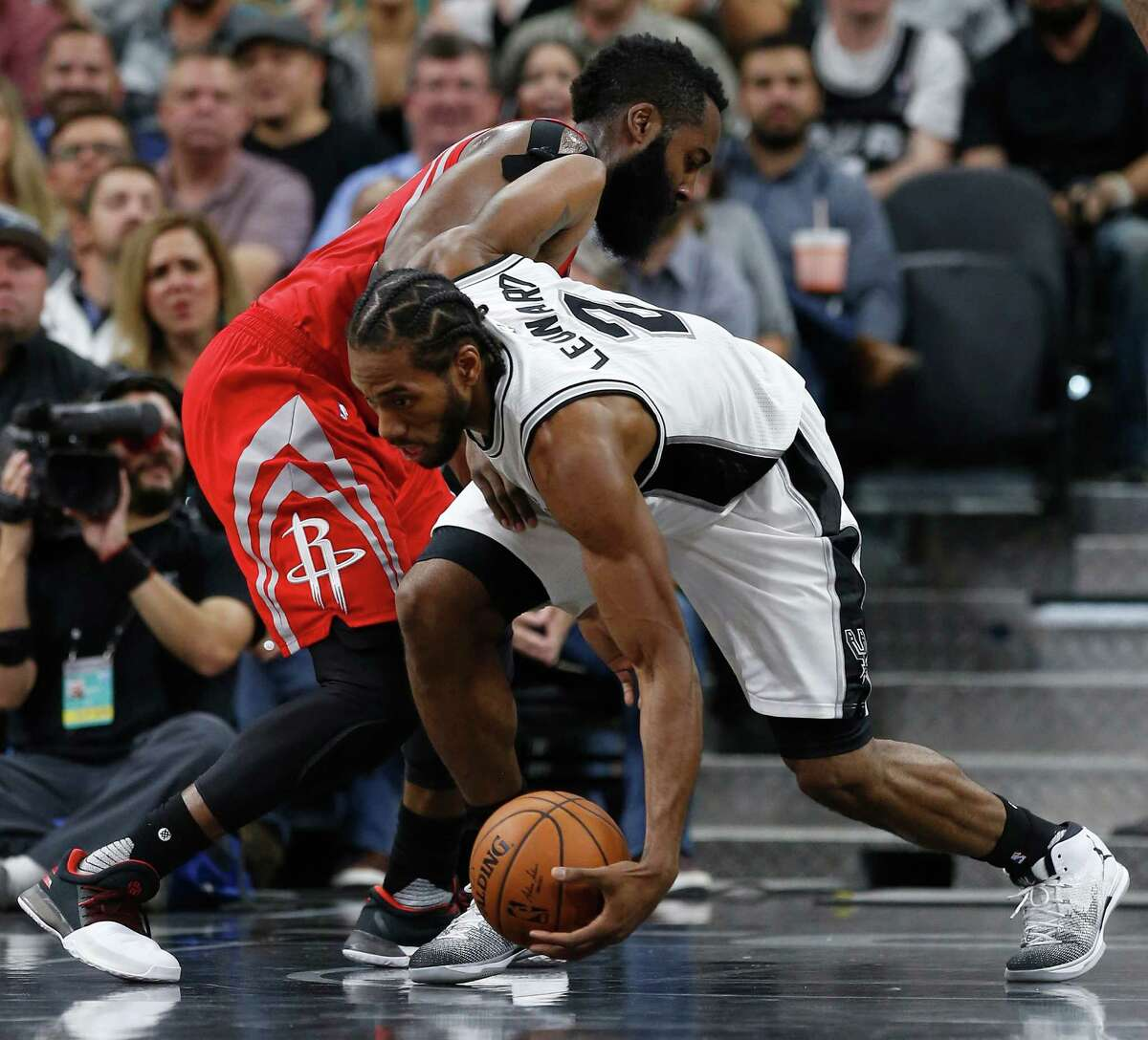 Spurs' Kawhi Leonard (02) scoops up a loose ball against Houston Rockets' James Harden (13) during their game at the AT&T Center on Wednesday, Nov. 9, 2016.