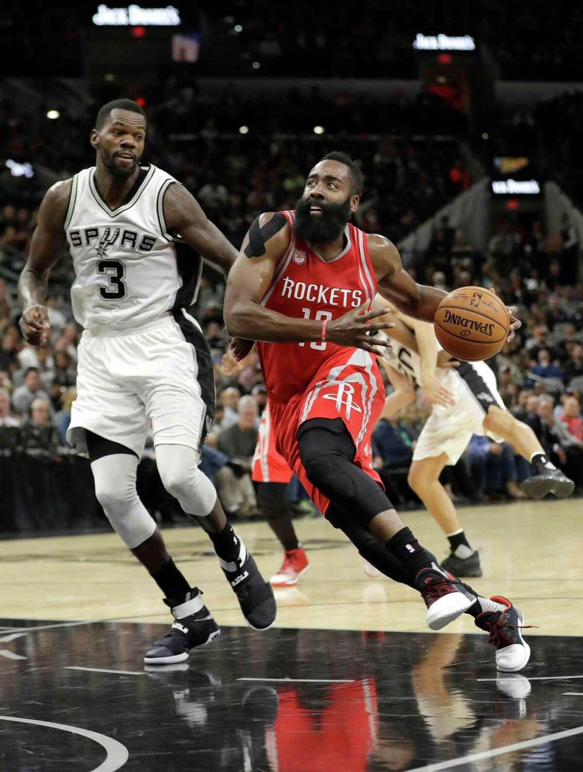 Houston Rockets guard James Harden (13) drives to the basket past San Antonio Spurs center Dewayne Dedmon (3) during the first half of an NBA basketball game, Wednesday, Nov. 9, 2016, in San Antonio. (AP Photo/Eric Gay)