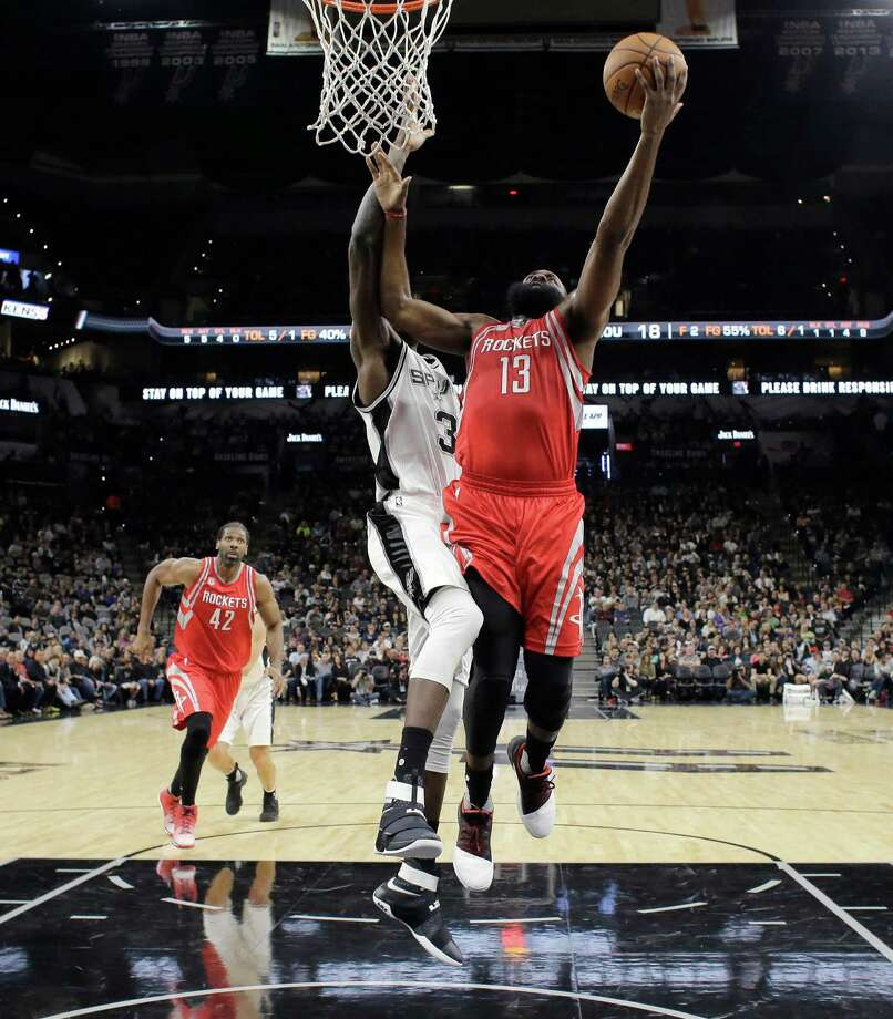 Houston Rockets guard James Harden (13) drives to the basket past San Antonio Spurs center Dewayne Dedmon (3) during the first half of an NBA basketball game, Wednesday, Nov. 9, 2016, in San Antonio. (AP Photo/Eric Gay) Photo: Eric Gay, Associated Press / Copyright 2016 The Associated Press. All rights reserved.