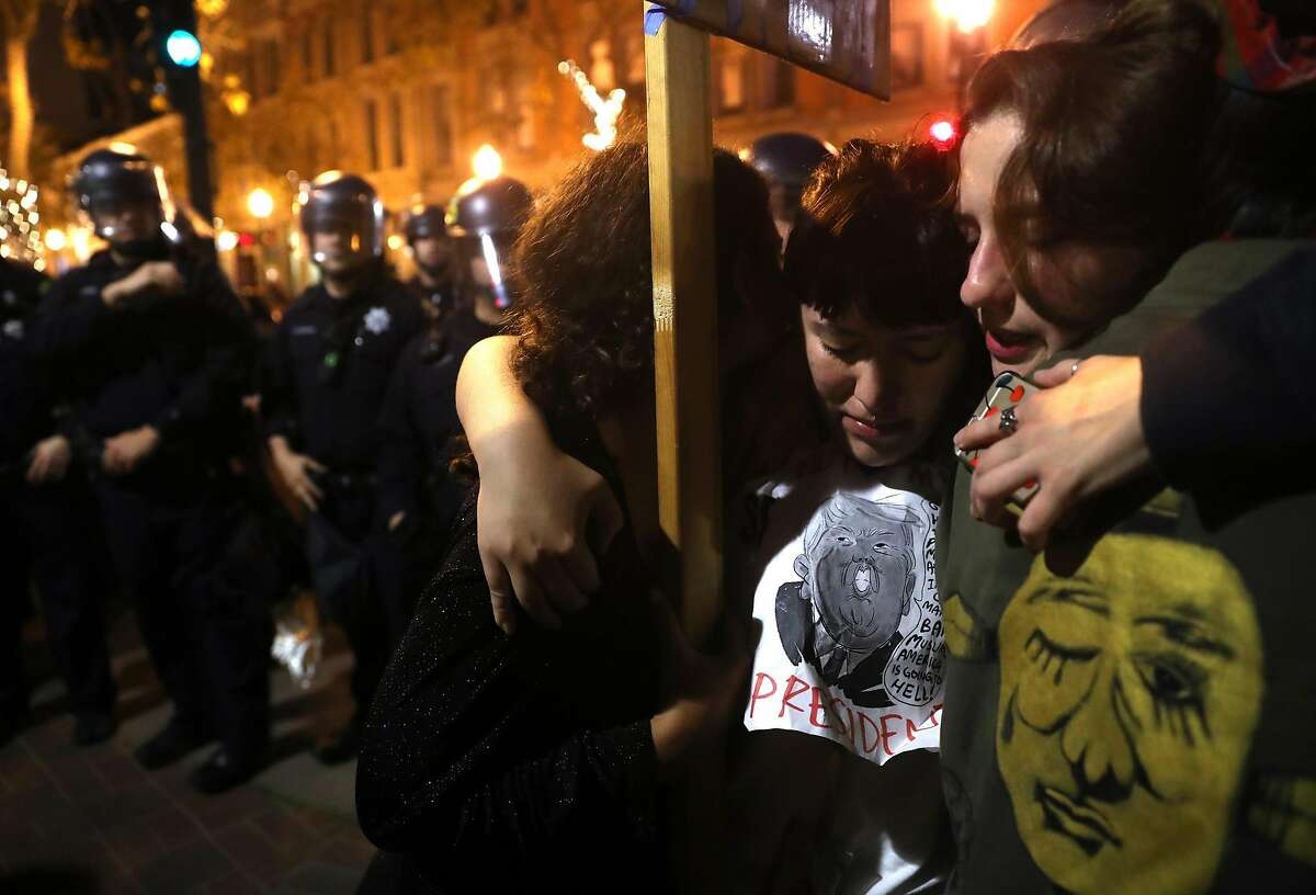 Three young woman embrace as Oakland Police advance down the street during an anti Donald Trump march in Oakland, Calif., on Wednesday, November 9, 2016.