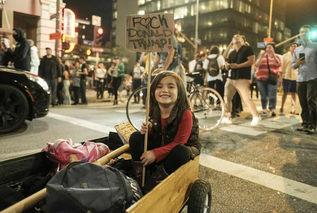 A child holds a placard as demonstrators gather to protest a day after President-elect Donald Trump's victory, at a rally outside Los Angeles City Hall in Los Angeles, California, on November 9, 2016. Protesters burned a giant orange-haired head of Donald Trump in effigy, lit fires ins the streets and blocked traffic lanes late on November 9 as rage over the billionaire's election victory spilled onto the streets of US cities. From New York to Los Angeles, thousands of people in around 10 cities rallied against the president-elect a day after his stunning win, some carrying signs declaiming