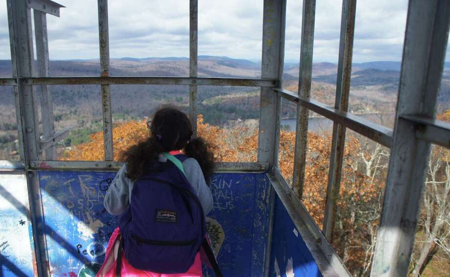 An intrepid young hiker peers out the windows of the Kane Mountain firetower near Caroga Lake. (Gillian Scott / Special to the Times Union) Photo: Picasa