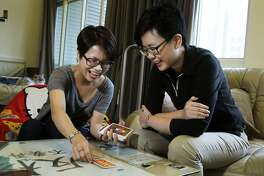 In this photo taken on Thursday, Nov. 3, 2016, Log Chen, right, and her partner Chalynn Hsueh joke as they lay out astrology cards in their home in Taipei, Taiwan. Alongside its vibrant youth culture, gay and lesbian causes have gone from scorn to acceptance in barely a generation, to the point that parliament is now expected to legalize same-sex marriage within months. For Chen, a Tarot card fortune teller in Taipei, legalized marriage would mean she and her partner of three years could make future plans with more confidence. (AP Photo/Chiang Ying-ying)