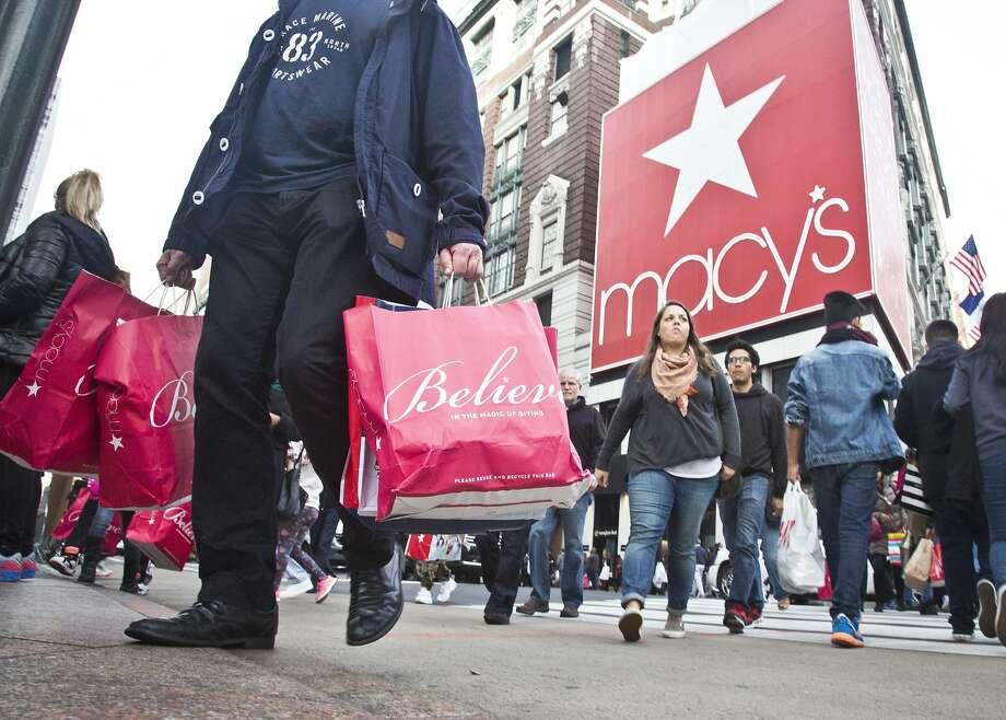Shoppers carry bags as they cross a pedestrian walkway near Macy's in Herald Square,  in New York last year.  Photo: Bebeto Matthews, Associated Press