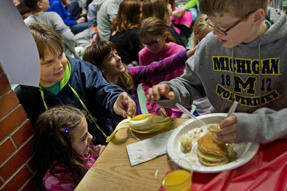 "ERIN KIRKLAND | ekirkland@mdn.net Northeast sixth grader Emma Green, 11, asks for pancakes as classmate Lars Larsen, 12, tries to steal classmate Brendan Hogan's, 12, banana on Friday at Northeast Middle School's Hunger Banquet. Sixth graders were divided into 1st, 2nd and 3rd world countries and were given appropriate breakfasts — a full breakfast, rice and beans and just rice. After seeing the pancakes and sausages that the 1st world was being served, the 3rd world students began chanting ""We want pancakes!"" until teacher Jennifer Suarez, who organized the event, calmed them down and reminded them that many in 3rd world countries sometimes only have a small amount of rice for a day's worth of food. Photo: Erin Kirkland/Midland Daily News"