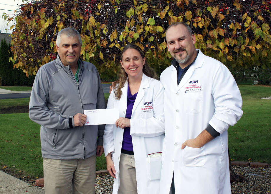 On behalf of Marlette Regional Hospital, nurse practitioner Kimberly Verellen (center) and Dr. Daniel Kulick (right) of Family HealthCare of Brown City presents a donation to Brown City Schools Athletic Director Tony Burton (left).
