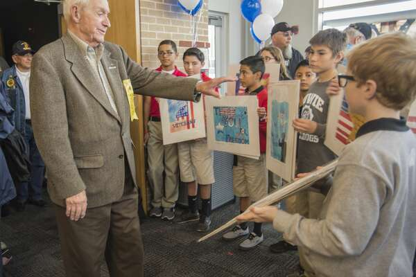 Veterans are each given a patriotic artwork as a memento Thursday 11-10-16 folowing the MISD Veterans Day Program at Bowie Fine Arts Academy with U.S. Ovation, a musical and comedy variety show along the lines of USO performances during past wars. Tim Fischer/Reporter-Telegram