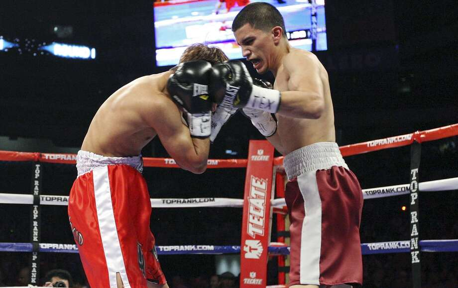 Richard Hernandez (left) is hit by Adam Lopez during the first round of their bantamweight fight on Feb. 4, 2012 at the Alamodome. Lopez won by TKO in the first round. Photo: Edward A. Ornelas /San Antonio Express-News / © SAN ANTONIO EXPRESS-NEWS (NFS)