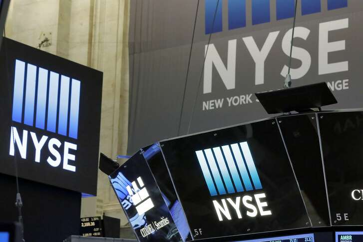The top of a trading post and an NYSE banner above the trading floor of the New York Stock Exchange are shown in this photo, Wednesday, Nov. 10, 2016. (AP Photo/Richard Drew)