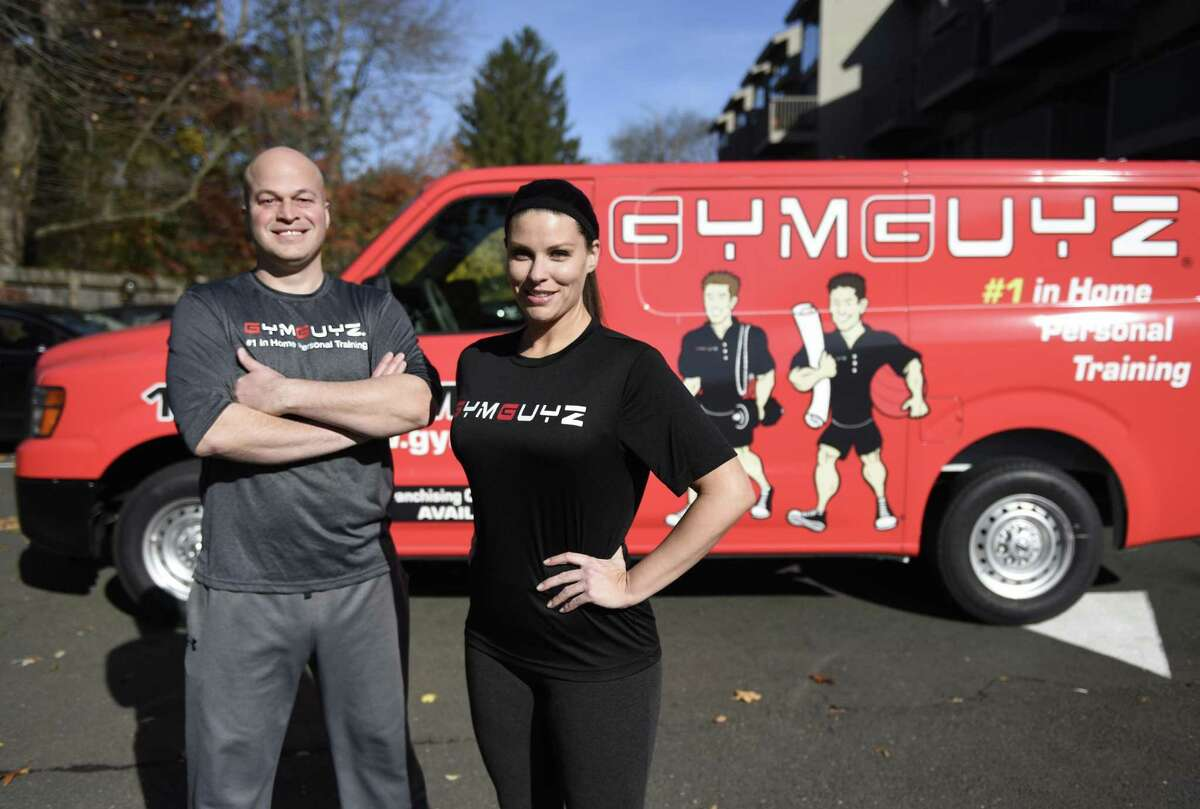 GymGuyz franchise owners Dave Dequeljoe and Amber Alagich pose in front of their personal training truck in Old Greenwich, Conn. Thursday, Nov. 10, 2016. GymGuyz provides on-site personal training to clients' homes, offices or sites of their choice with experienced trainers assisting with customized one-on-one workouts or inclusive group workouts.