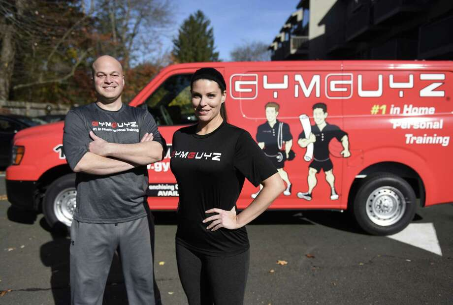 GymGuyz franchise owners Dave Dequeljoe and Amber Alagich pose in front of their personal training truck in Old Greenwich, Conn. Thursday, Nov. 10, 2016. GymGuyz provides on-site personal training to clients' homes, offices or sites of their choice with experienced trainers assisting with customized one-on-one workouts or inclusive group workouts. Photo: Tyler Sizemore / Hearst Connecticut Media / Greenwich Time