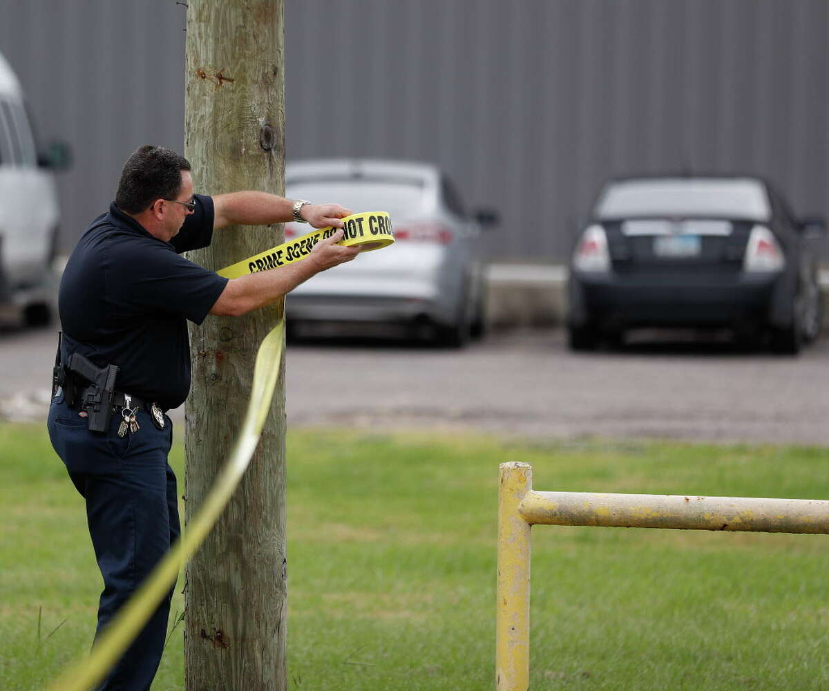 A Texas City Police officer puts up crime scene tape just after members of Equusearch had begun their search for Kirsten Fritch, 16, in the parking lot of Shenanigan's Night Club, Thursday,Nov. 10, 2016 in Texas City ,
