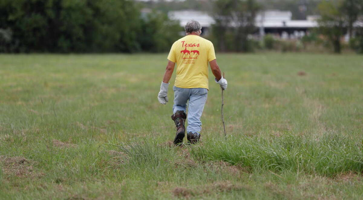 An Equusearch member walks in a field as they began searching for Kirsten Fritch, 16, in the parking lot of Shenanigan's Night Club, Thursday,Nov. 10, 2016 in Texas City. Fitch went missing after the murders of her mother and sister in Baytown.