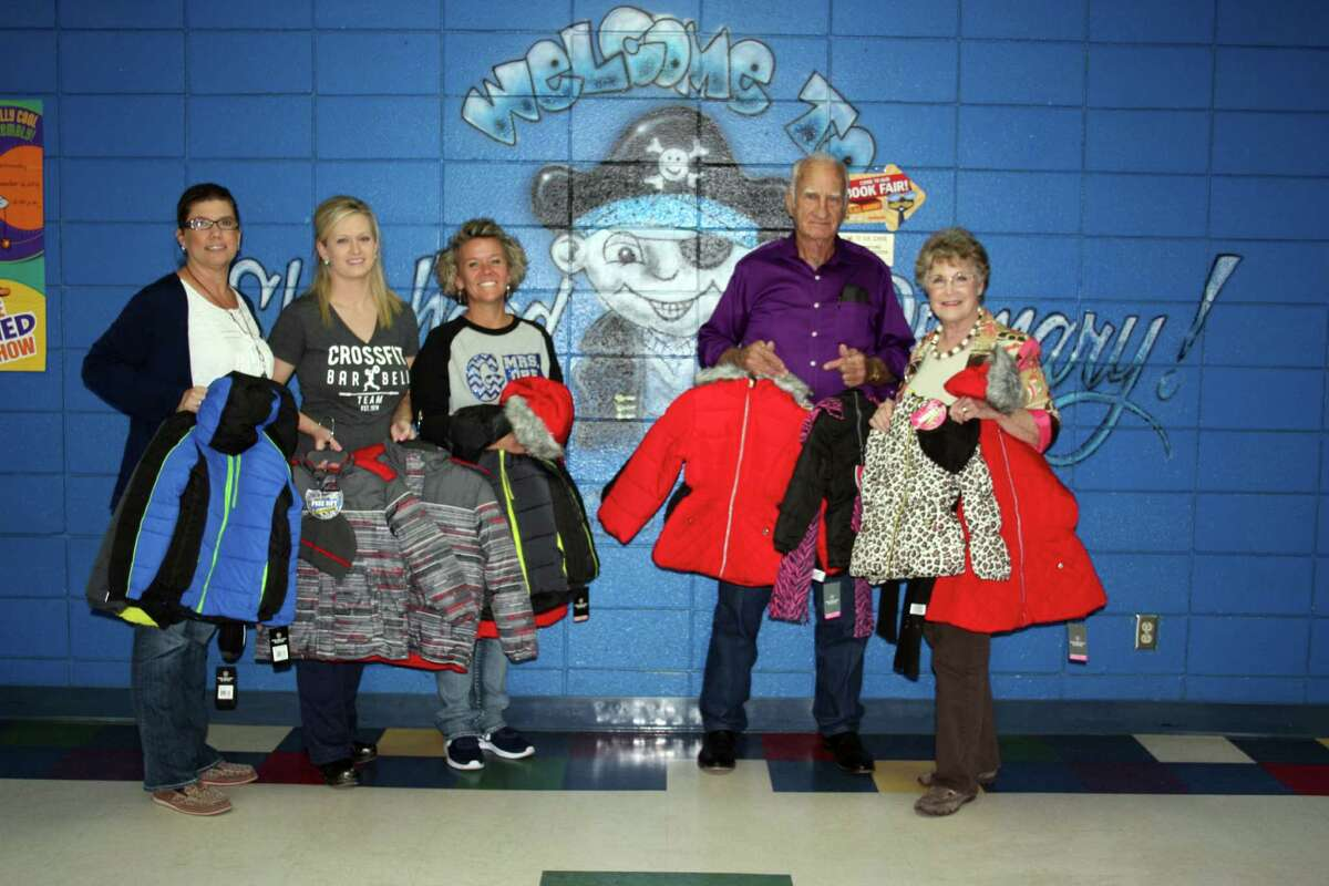 Shepherd Primary Principal Sandra Meekins, nurse Paige May and Assistant Principal Heather Gore accept a donation of coats, underwear and socks from Kenneth and Vada Syphrett, representatives of New Hope Baptist Church of Cleveland.