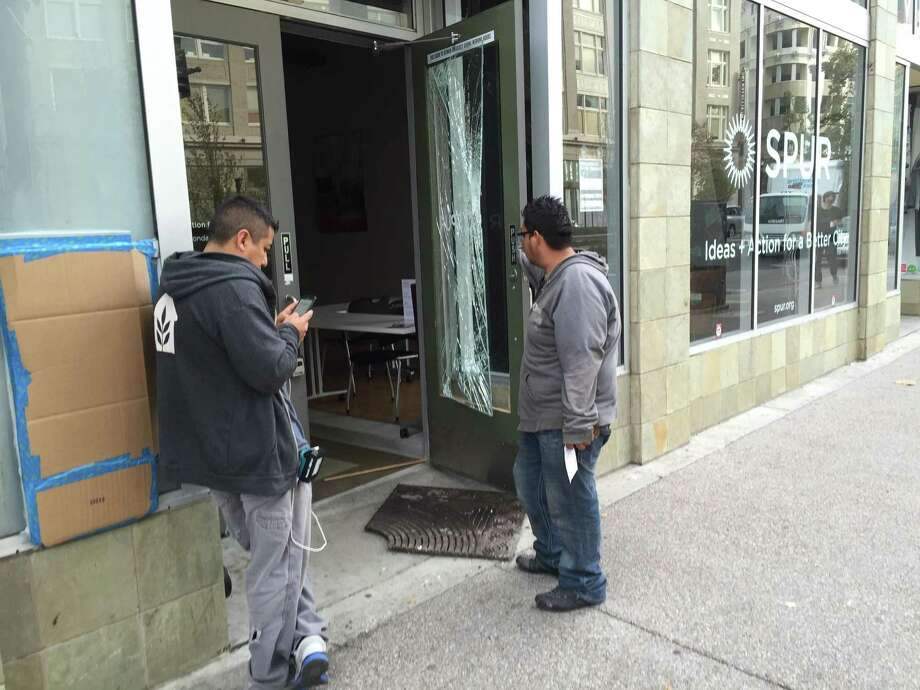 Two contractors look to replace a window at Spur Oakland that was shattered during protests in downtown Oakland the night before. Photo: Evan Sernoffsky / The Chronicle / /