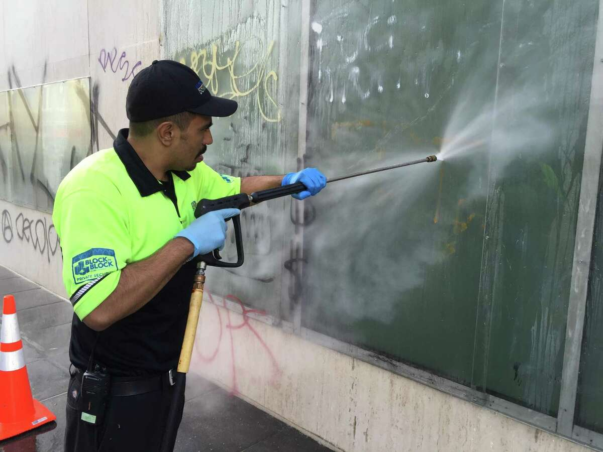 An Oakland city worker washes spray paint off of an Oakland building following anti-Donald Trump protests in 2016.