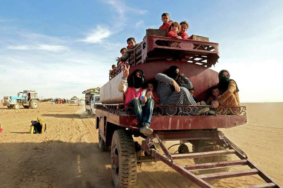 A child raises a victory sign while riding a towed storage tank carrying other Syrians fleeing areas controlled by jihadists of the Islamic State group, as they come to safety in areas held by by Kurdish-Arab Syrian Democratic Forces. Photo: DELIL SOULEIMAN, Stringer / AFP or licensors