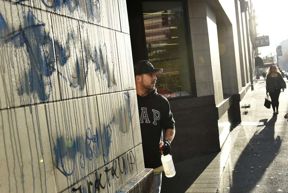 Gerardo Torres with RC Maintenance cleans graffiti off of Rite Aid on Broadway and 14th St. following overnight protests against the election of Donald Trump, in Oakland, CA, Thursday, November 10, 2016. Photo: Michael Short, Special To The Chronicle