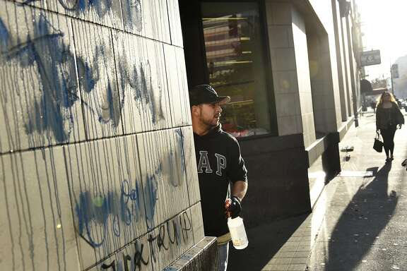 Gerardo Torres with RC Maintenance cleans graffiti off of Rite Aid on Broadway and 14th St. following overnight protests against the election of Donald Trump, in Oakland, CA, Thursday, November 10, 2016.