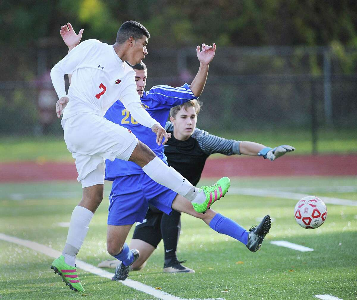 At left, Sebastian Hernandez of Greenwich gets off a shot that gets past Newtown keeper Cameron Trivers, right, for the first goal of the match during the boys high school Class LL soccer playoff game between Greenwich High School and Newtown High School at Cardinal Stadium in Greenwich, Conn., Thursday, Nov. 10, 2016. At center defending for Newtown is Hunter Procaccini. Greenwich advanced in the tournament, defeating Newtown 2-1.