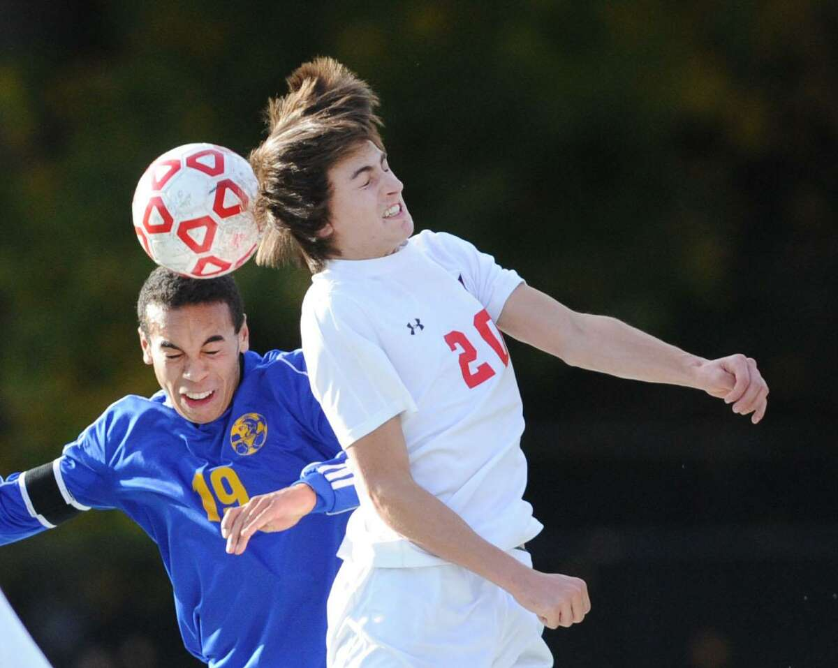 At left, Elliott Bennett of Newtown goes for a header against Timothy Bennett (20) of Greenwich during the boys high school Class LL soccer playoff game between Greenwich High School and Newtown High School at Cardinal Stadium in Greenwich, Conn., Thursday, Nov. 10, 2016. Greenwich advanced in the tournament, defeating Newtown 2-1.