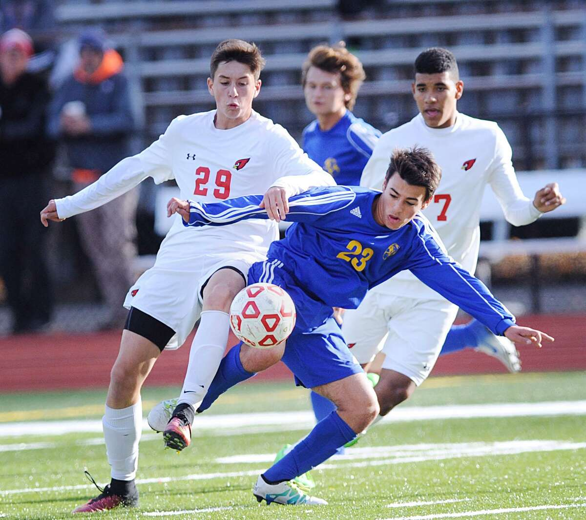 At left, Kai Lammers (29) of Greenwich goes for the ball along with Newtown's Adam Farley (23) during the boys high school Class LL soccer playoff game between Greenwich High School and Newtown High School at Cardinal Stadium in Greenwich, Conn., Thursday, Nov. 10, 2016. In background at right is Sebastian Hernandez (7) of Greenwich. Greenwich advanced in the tournament, defeating Newtown 2-1.