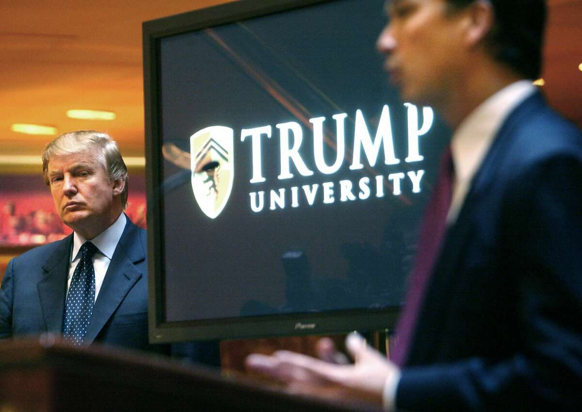FILE- In this May 23, 2005 file photo, then real estate mogul and Reality TV star Donald Trump, left, listens as Michael Sexton introduces him at a news conference in New York where he announced the establishment of Trump University. Trump is scheduled to go on trial this month in a class-action lawsuit against him and his now-defunct Trump University, potentially taking the witness stand weeks before his inauguration as president of the United States. U.S. District Judge Gonzalo Curiel, the Indiana-born jurist who was accused of bias by Trump during the campaign for his Mexican heritage, will hold a hearing Thursday, Nov. 10, 2016, on jury instructions and what evidence to allow at trial. (AP Photo/Bebeto Matthews, File)