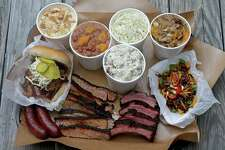 Meats and sides at Two Bros. BBQ Market, closkwise from left: sausage, the Big Bro sandwich, banana pudding, BBQ beans, potato salad, creamy cole slaw, peach cobbler, chopped beef Frito pie, cherry glazed baby back ribs and brisket.
