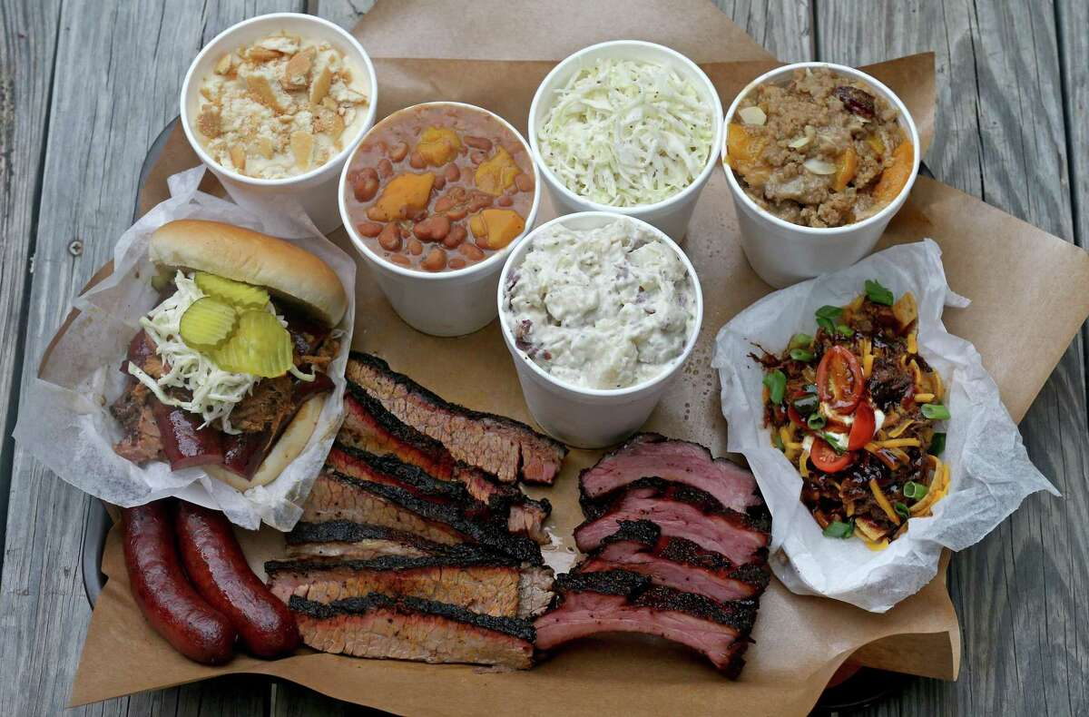 Sausage (from left clockwise), Big Bro Sandwich, banana pudding, beans, potato salad, cole slaw, peach cobbler, chopped beef Frito pie, cherry glazed baby back ribs and brisket from Two Bros. BBQ Market